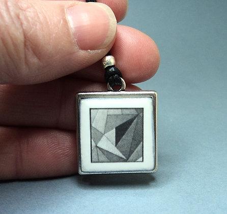 médaillon pendentif en céramique motif origami noir et blanc