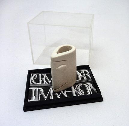 petit personnage blanc en céramique dans une boîte transparente