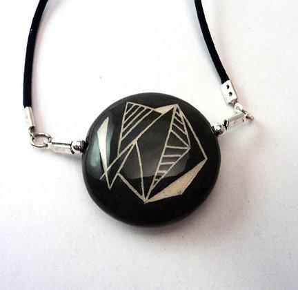 pendentif rond noir avec graphismes géométriques
