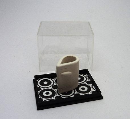 petit personnage sculpté dans une boîte vitrine transparente sol motifs géométriques