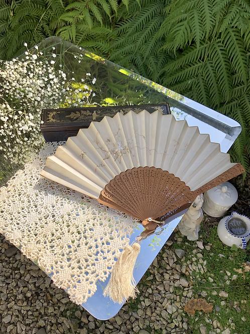 Abanico de madera tallada y seda bordada a mano .