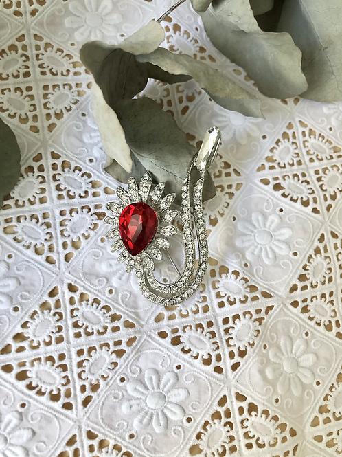 Broche de cristal con piedra roja.