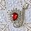 Thumbnail: Broche de cristal con piedra roja.