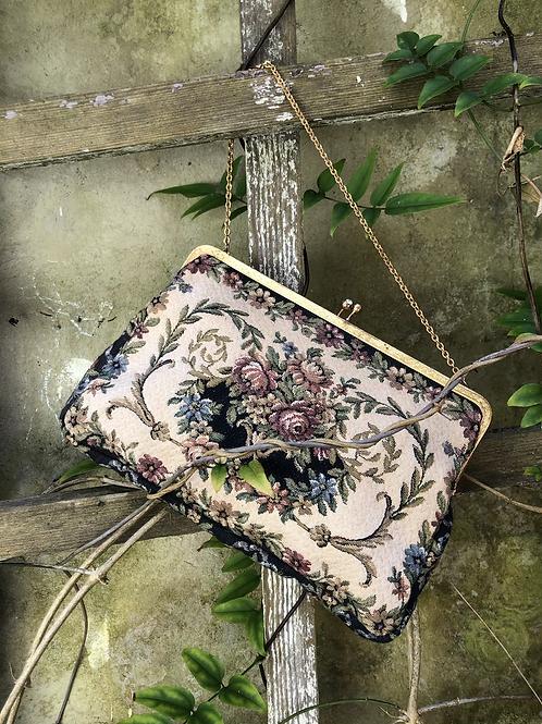 Bolso de tapicería con asa dorada.