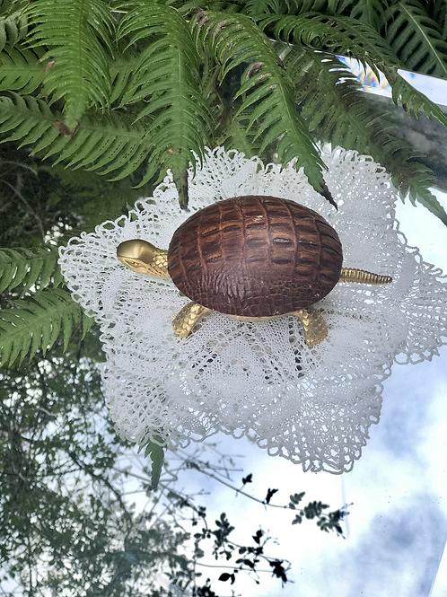 Timbre de bronce y piel con forma de tortuga .