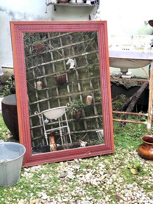 Espejo con marco de madera trenzado.