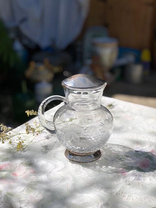 Jarra de cristal tallado con tapa y pié de plata.