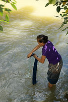 Tai Lue woman washing indigo yarns in the river