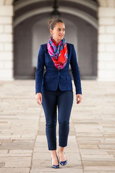 Woman, navy suit, red scarf, bun, heels, trousers, blazer