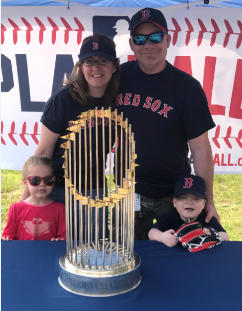 The Murphy family smile behind the 2013 Red Sox World Series trophy. Georgia, Susan, Peter and Donovan smile together wearing baseball attire.