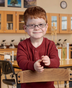 Donovan smiles for a school picture, wearing a red shirt  and glasses and sporting his characteristic red hair.