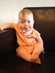 Baby Donovan sits up against the arm of the couch, his tuft of orange hair curling over his forehead, and wearing an orange striped romper and a tentative smile.