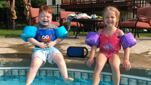 Emerson is sitting on the side of a swimming pool with his younger sister, Emerson. They are both wearing swimsuits and water-wings (arm-bands) and smiling into the camera, ready to hop into the water.
