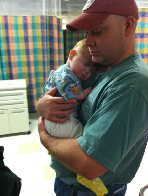 Peter holds his young son, Donovan in his arms while they wait in a hospital warm.
