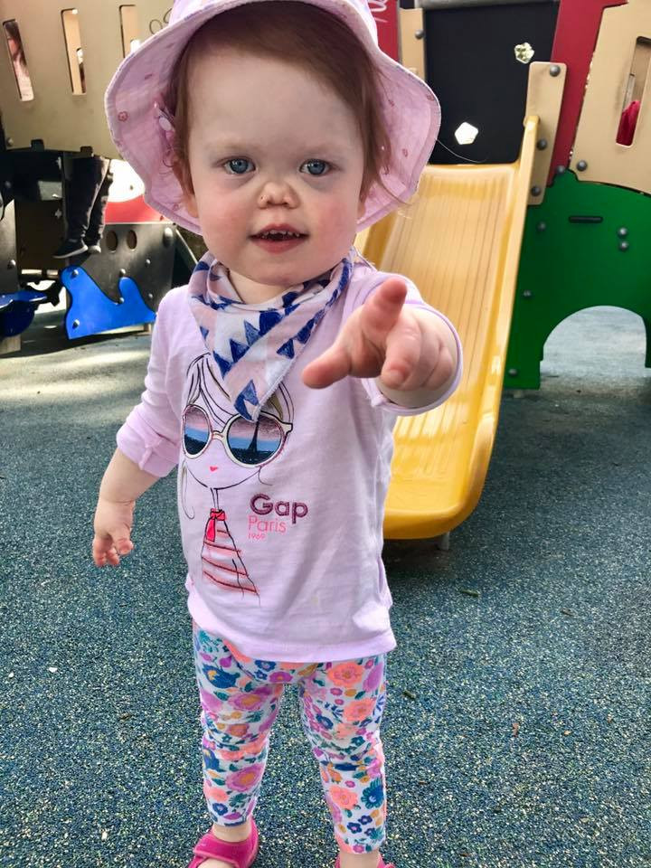 Frankie points to the camera, wearing a pink hat, a pink top and flowery leggings.