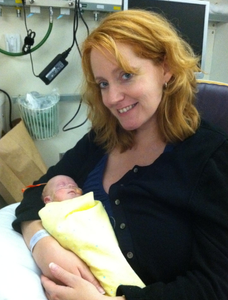Baby Donovan is sleeping, wrapped in a yellow cloth and lies in the arms of his mom, Susan, who is smiling.