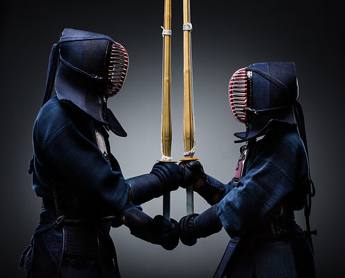 Two kendo fighters with shinai opposite