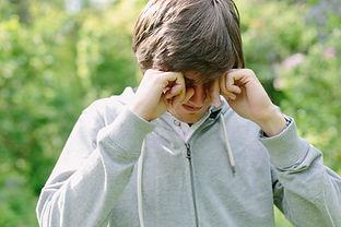 Young man having eye pain and rubbing hi