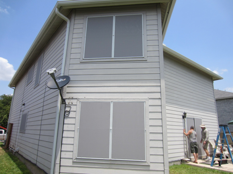 Gray fabric solar window screens.