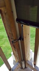 Outdoor patio shades tie down hook into cedar hand rail.