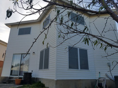Grey solar screens for windows of Buda TX home.