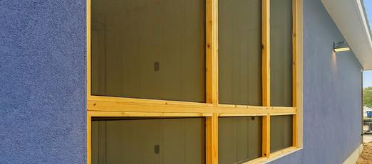 Bug screens installed in wood framed patio enclosure.