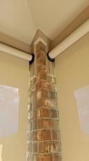 Installing outdoor roller blinds to a brick corner.