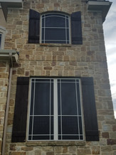 Arched solar window screens with grid patterns.