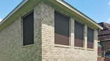 Solar screens for windows in Round Rock using Choc 90% Champagne frame.