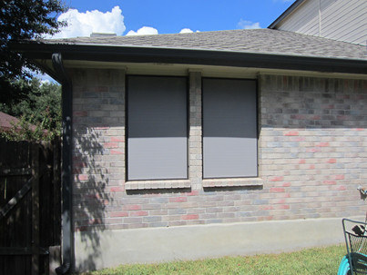 Grey solar screens installed w/ brown frame as a visual accent.