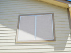 Stucco Solar Screens with white frame, side by side windows.