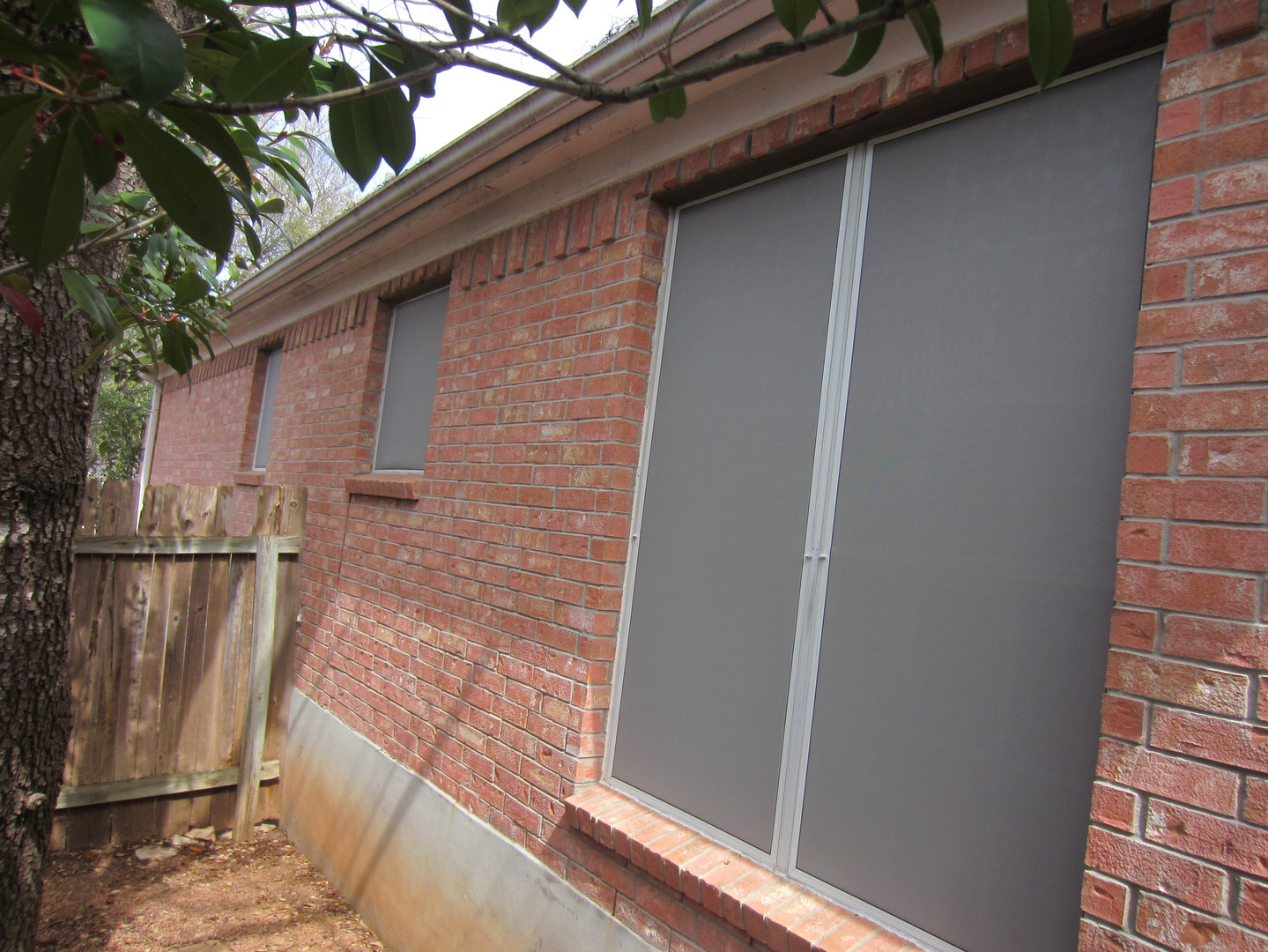 Grey fabric solar window screens.