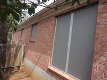 Grey fabric solar window screens.