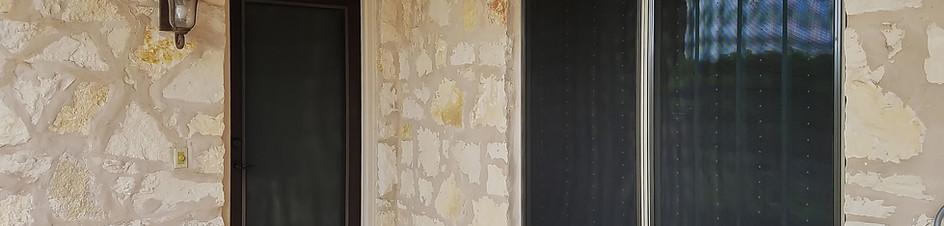 Brown frame black fabric solar screen for back door.