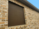 Covering a glass block bathroom window with a solar screen.