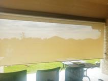 Beige White sun control Round Rock outdoor roll down shades.