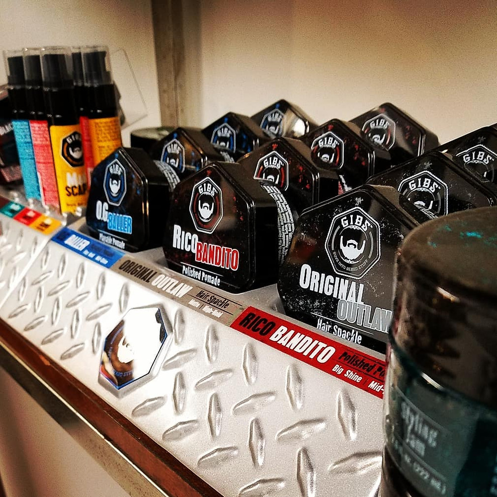 beard hair and skin oils in bottles displayed next to mens hair products shaped like pucks.