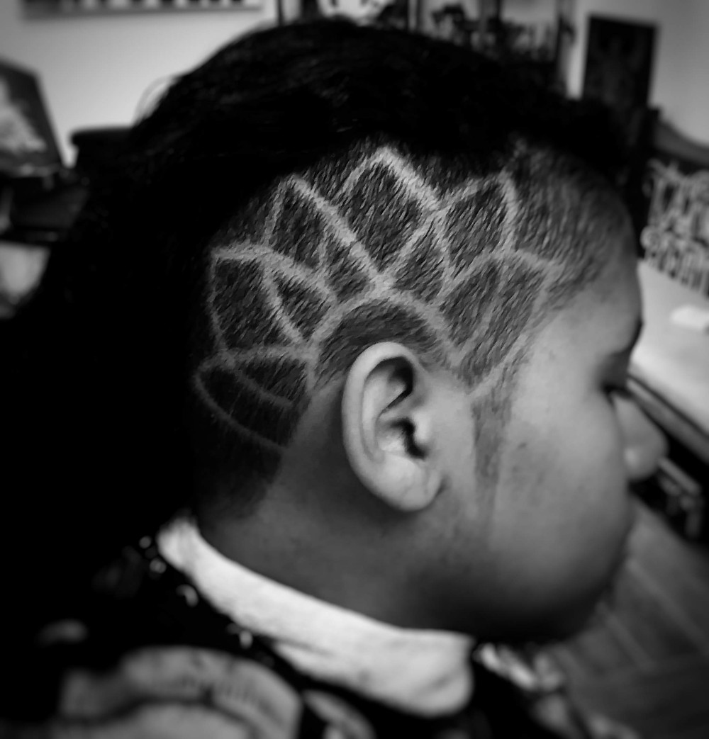 Oblong lines create a lotus flower tattoo above the ear.