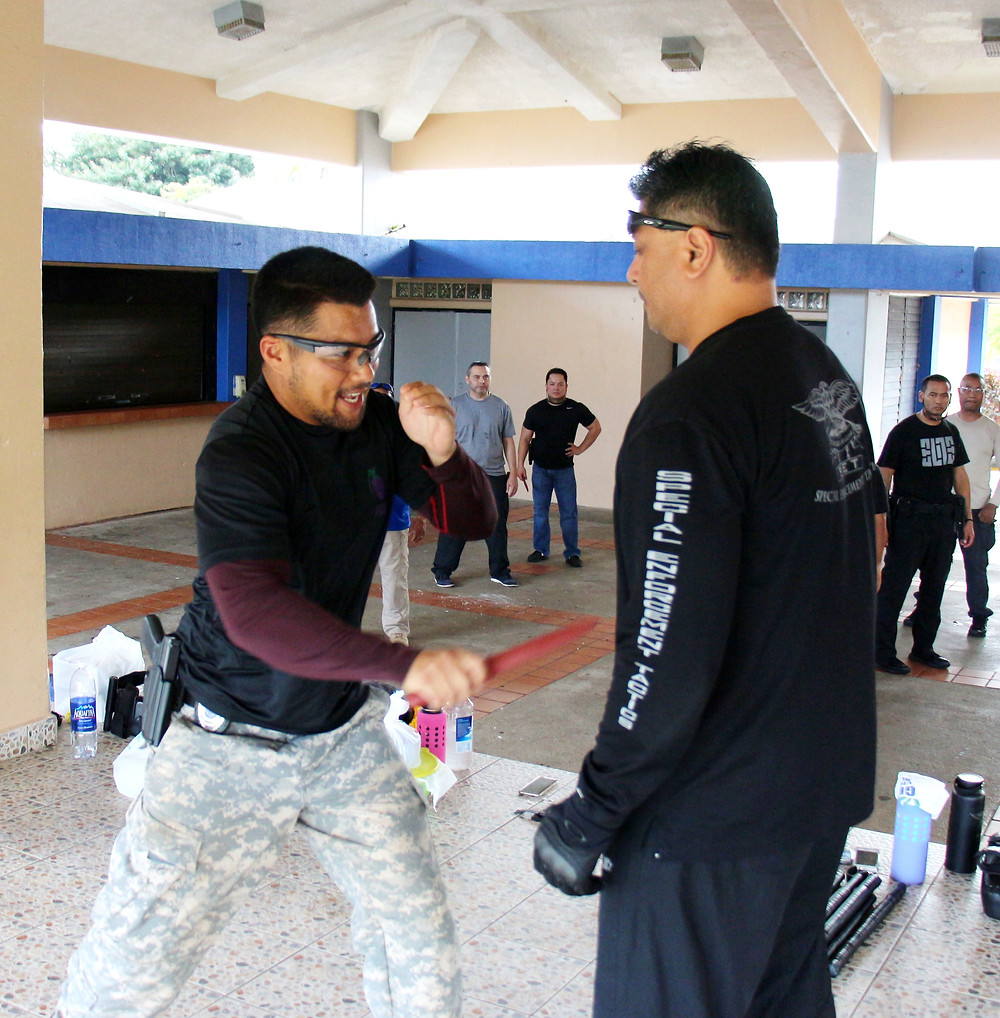 Probation Officer Randall Yasuhiro demonstrates a knife attack on Training Officer/Deputy Marshal Vince Naputi during the Judiciary of Guam Defensive Tactics Training