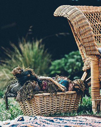 Basket filled with rolled Pashmina next wicker chair outside
