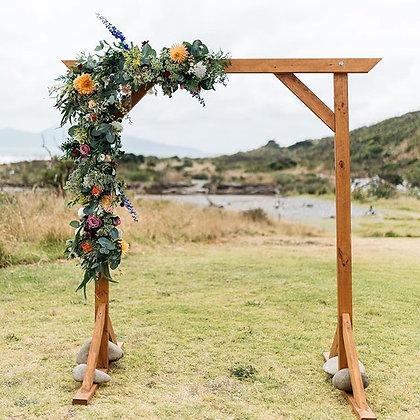 Wooden wedding arch with flowers un coastal park