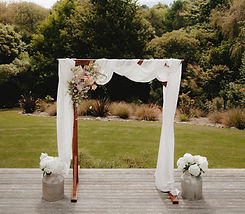 Wooden wedding arch draped with fabric and with flowers