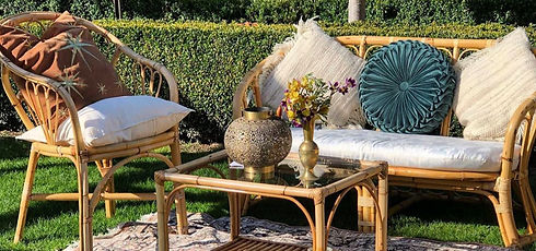Handmaid Hire cane furniture with cushionsa and Persian rug in garden