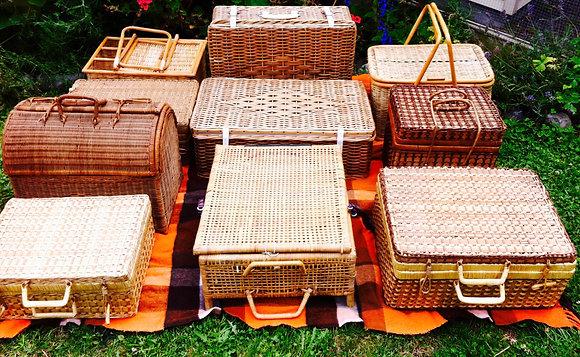 Collection of vintage picnic baskets and hampers on a vintage blanket