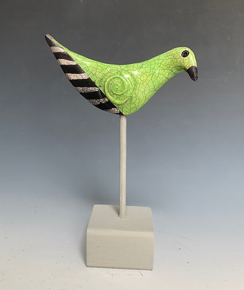 """""""Going Green"""" is a raku fired clay bird on a grey wooden base by JoAnne Bedient."""
