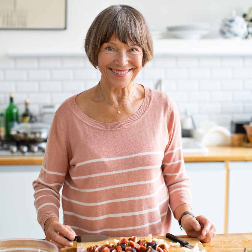 Older woman smiling in the kitchen chopping fruit.