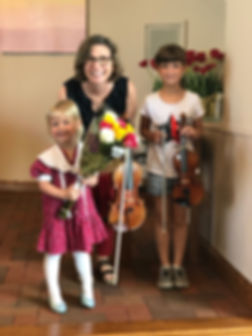 Two girls taking music lessons with their Suzuki teacher