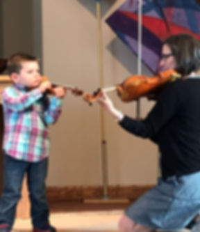 Boy playing viola with his teacher
