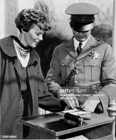 Amelia Earhart getting finger printed in 1936