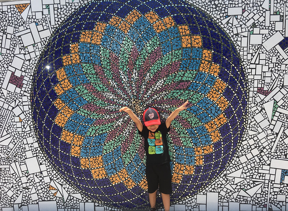 Boy poses in front of colorful mosaic artwork in downtown Puerto Vallarta, Mexico.